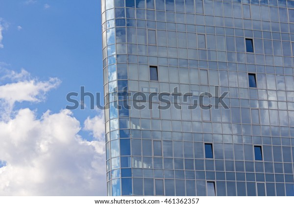 Facade of modern glass blue office and sky with clouds