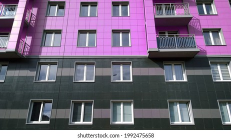 Facade of new multicolor residential building. Rising prices for purchase, sale and rental of real estate. Inexpensive apartments. Comfortable housing. Cityscape. City living. Windows and balcony.