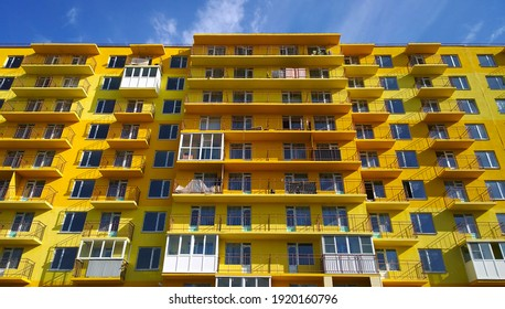 Facade of new multi-story residential building. Architecture background. House Share. Real estate investing. Sale, rental and insurance apartment in crisis. Housing development. Illuminating yellow.