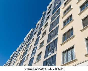 Facade of a new residential building. Modern buildings. Plaster beige wall