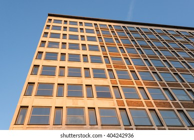 Facade of an office building with warm sunset light beaming on it. View from below.