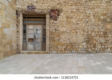 Facade of old abandoned stone bricks wall with broken weathered wooden door