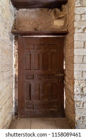Facade of old abandoned stone bricks wall with grunge weathered wooden door, Old Cairo, Egypt