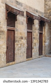 Facade of old abandoned stone bricks wall with three weathered wooden doors and opening covered with wooden grid, Old Cairo, Egypt