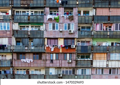 Facade of old apartment house. Slum house. Linen is dried on the balconies. Problem of overpopulation and poverty