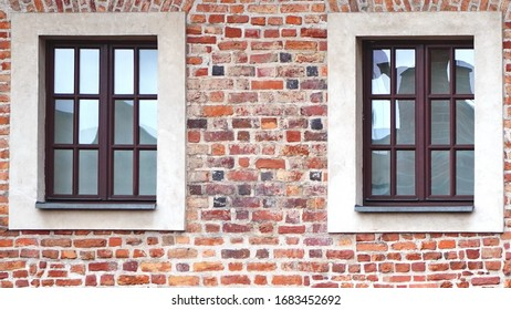 The facade of an old brick building with windows or cornices. Old brick walls
