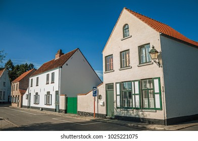 Facade of old brick houses on an empty street, in the late afternoon light at Damme. A quiet and charming countryside old village near Bruges. Northwestern Belgium.