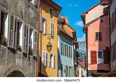 Facade of old and colorful buildings with windows and blue sky in the background. City center of Annecy, France