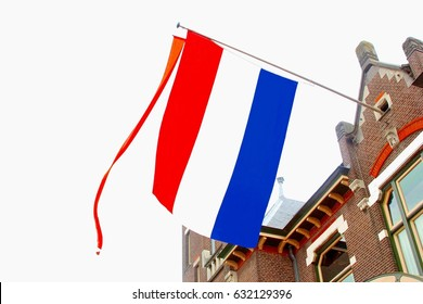Facade of old Dutch house with national flag and orange streamer, Netherlands.
