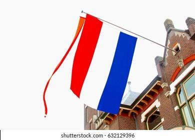 Facade of old Dutch house with waving national flag and orange streamer. Koningsdag (Kingsday) and Bevrijdingsdag (Liberation Day),  Netherlands.