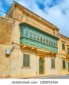 The facade of the old edifice with traditional wooden Maltese balony, Nadur, Gozo, Malta.