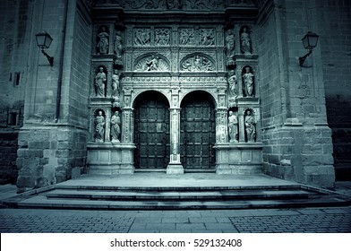 Facade of old medieval church, detail of a wooden door and gothic sculptures, City Tours