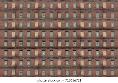 Facade of an old red brick wall with windows.