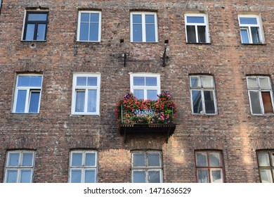 Facade of an old slum house with decorated balcony and damaged brick walls in a poor and criminal district. Location: Brzeska street, Praga district of Warsaw city, Poland