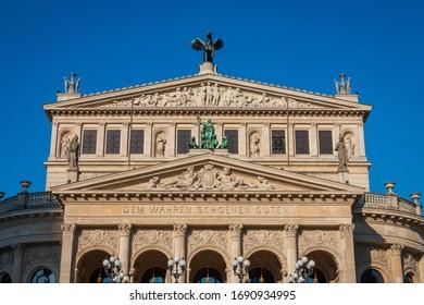 "Facade of opera house ""Alte Oper Frankfurt"" (old opera) with inscription ""dem wahren schönen guten"", translated in English to the true beautiful good) and incidental people"