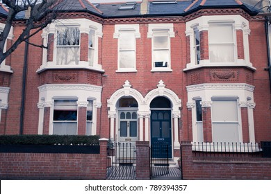 Facade of an opulent restored Victorian house in red bricks and white finishing in Clapham, South London, UK. Vintage matte effect