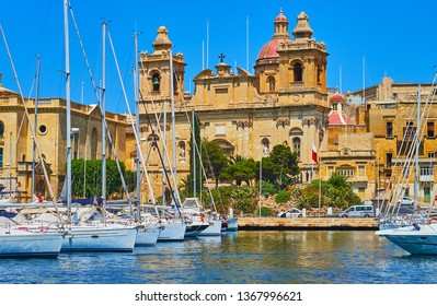 The facade of the ornate St Lawrence church from Vittoriosa marina with docked yachts on the foreground, Malta.