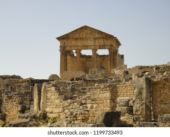 Facade And Pediment Of The Main Roman Capitol Temple At Dougga Or Thugga The  Romano-Berber City In Northern Tunisia.  The Temple Is Dedicated To The Gods Jupiter, Juno, And Minerva