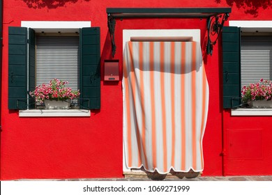 The facade of a red-painted house with beautiful Mediterranean-style shutters