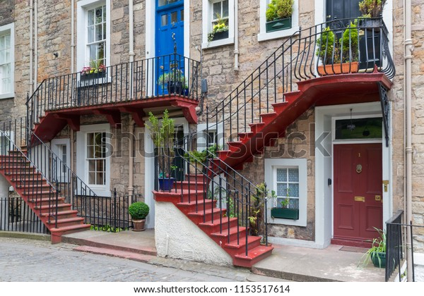 Facade of residential homes with two floors and a staircase in front of the house