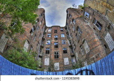 Facade of ruined old vintage red brick ghetto house at Kamienico, part of former Jewish ghetto, Warsaw city, Poland on blue cloudy sky - HDR (High Dynamic Range) image through fisheye lens
