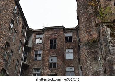 Facade of ruined old vintage red brick house with broken windows (location: Kamienico, part of former Jewish ghetto, Walicow street, Warsaw city, Poland)