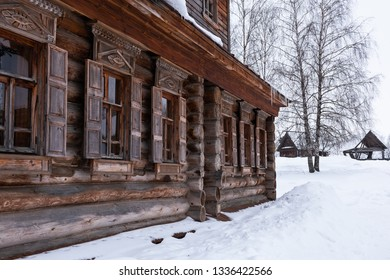 The facade of the Russian wooden house with six windows in winter
