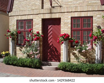 Facade of the small brick house decorated with flowers. Historical fisherman's quarter Holm in Schleswig city, Schleswig-Holstein, North-West Germany