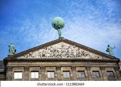 The facade and statues of the 17th century Royal Palace of Amsterdam, otherwise known as the Dam Palace, in Amsterdam, Netherlands. Atlas is seen holding the world on his shoulders in the centre.