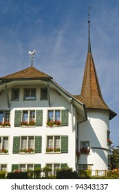 Facade of a Swiss house with green shutters and a circular tower topped with a spire