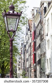 Facade of traditional apartment buildings in Amsterdam, Netherlands, with lamp.
