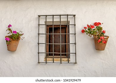 Facade of traditional Spanish house with flower pots with geraniums and fenced window.