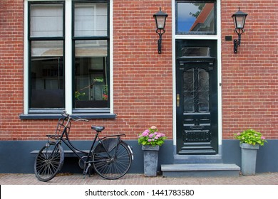 Facade of typical Dutch house with brick walls, steps, front door windows and black bike in popular neighborhood street, Netherlands