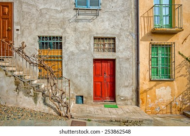 Facade of typical italian house with colorful windows and doors in town of Saluzzo in Piedmont, Northern Italy.