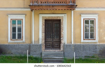 Facade of an uninhabited traditional house with a wooden balcony over the entrance door