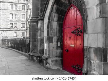 Facade of a vintage Red Door in Edinburgh, Scotland. Beautiful Old city red door. Front view of a bright red vintage front door.