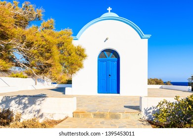 Facade of white typical Greek church with blue door on coast of Karpathos island, Ammopi village, Karpathos island, Greece