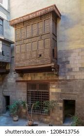 Facade of Zeinab Khatoun historic house with Mamluk era style oriel window covered by interleaved wooden grid (Mashrabiya), located near to Al-Azhar Mosque in Darb Al-Ahmar district, Old Cairo, Egypt