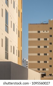 Facades of apartment blocks in an area of new housing development in the Middle East against a blue sky.