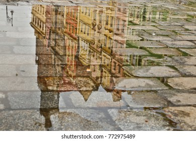 Facades of buildings at market square reflected in puddle in Wroclaw, Poland