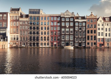 Facades of colorful traditional old living houses along the canal coast in old Amsterdam, Netherlands. Warm vintage tonal correction filter effect, retro style