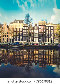 Facades of dutch houses over canal with mirror reflections, Amstardam, Netherlands, retro toned