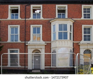 the facades of large abandoned derelict brick houses on a street with boarded up doors and windows behind a fence in southport merseyside