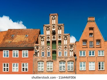 Facades of the old historiacal buildings made of red brick. Blue sky on the background. Luneburg, Germany