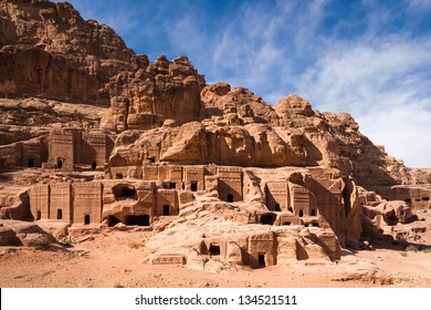 Facades of old rock houses against a blue sky with white clouds in ancient Petra in Jordan