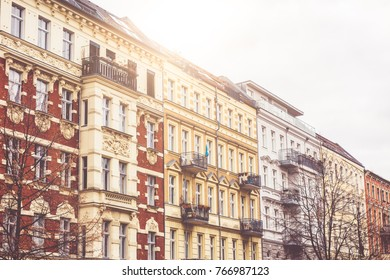 Facades of tenement buildings with balconies at sunset