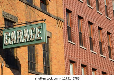 Facades of two brick buildings and an old neon sign for a parking garage in Manhattan