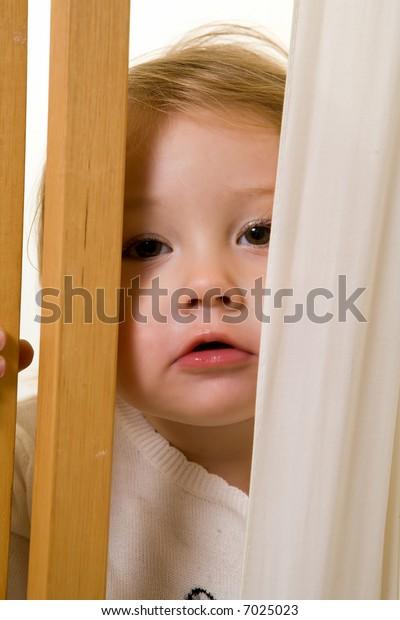 Face of an adorable caucasian blond baby girl toddler peeking through a curtain