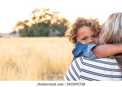 Das Gesicht eines bezaubernden, geschmeidig haarigen afroamerikanischen Jungen in den Armen seiner Mutter im Sonnenlicht im Freien. Ein fröhlicher und inhaltlicher Ausdruck, wie die Mutter ihrem Sohn Liebe und Zuneigung zeigt