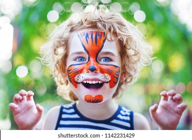 face art painting like tiger, little boy making face painting, halloween party, child with funny face painting, little cute boy with face art on birthday party close up, smiling boy with curly hair